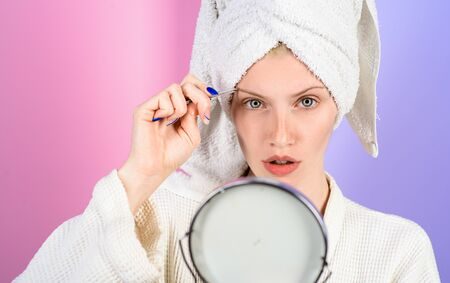 Woman pluck eyebrows looking in mirror. Epilate eyebrows. Woman with tweezers. Girl makeup process. Eyebrows beauty care. Beauty tools. Correction procedure in beauty salon.