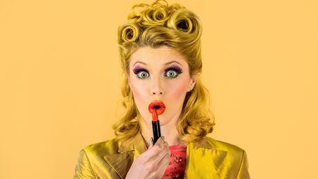 Mujer pin-up aplicando lápiz labial. Modelo rubio retro con pelo rizado aplicando lápiz labial. Pintalabios rojo. Maquillaje perfecto, cosmética, rostro. Maquillaje de niña modelo. Piel perfecta. Corrección de labios. Listo para la fiesta. Foto de archivo