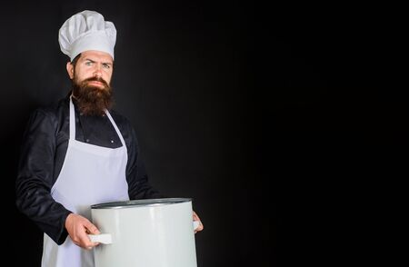 Cook in white apron with pot. Cooking, culinary, cuisine. Food preparation. Professional cook holds kitchen utensil. Bearded chef in kitchen holds big pot. Male chef. Chef man prepares meal. Copyspace Stock Photo