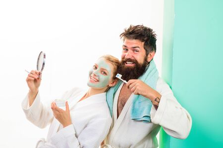Morning procedures in bathroom. Awakening. Bearded man with toothbrush. Woman with facial mask. Morning treatments. Family life. Husband and wife. Happy couple in morning. Health. Morning routine. Фото со стока