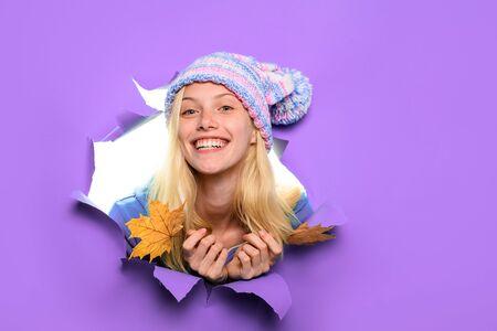 Gelukkig meisje in hoed met esdoornbladeren. Gelukkig meisje houdt blad vast. Herfst verkoop. Herfst sfeer. Geel esdoornblad. Korting. Verkoop. Glimlachende vrouw met herfstbladeren die door een papieren gat kijken. Ruimte kopiëren. Stockfoto