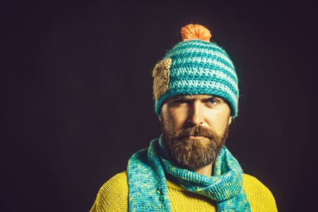 Stylish man wrapped in warm knitted scarf. Autumn, winter, fashion. Fashionable man with scarf and sweater in autumn/winter time. Bearded man in scarf and sweater. Men winter fashion, european style 免版税图像