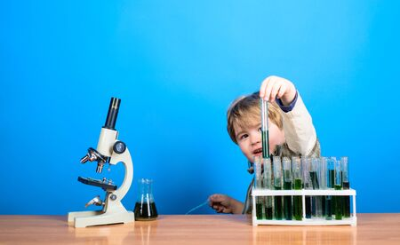 Chemistry. Science. Experiment. Education. Study. Smart boy working with microscope and test tubes. Little kid with test tubes. Modern technology. Stock Photo