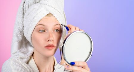 Woman pluck eyebrows looking in mirror. Epilate eyebrows. Woman with tweezers. Girl makeup process. Eyebrows beauty care. Beauty tools. Correction procedure.