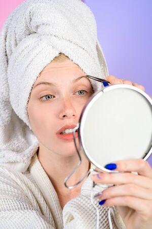 Frau zupft Augenbrauen im Spiegel. Augenbrauen epilieren. Frau mit Pinzette. Make-up-Prozess für Mädchen. Schönheitspflege der Augenbrauen. Schönheitswerkzeuge. Korrekturverfahren im Schönheitssalon.