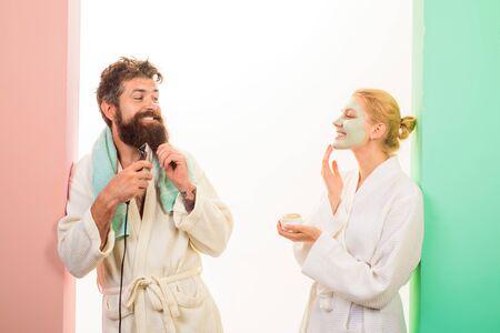 Morgen. Paare, die sich morgens im Badezimmer auf die Arbeit vorbereiten. Schöner Mann rasiert Bart mit Elektrorasierer, Mädchen, das Gesichtsmaske anwendet. Mann, der Bart mit Trimmer rasiert, Frau, die kosmetische Maske auf Gesicht aufträgt