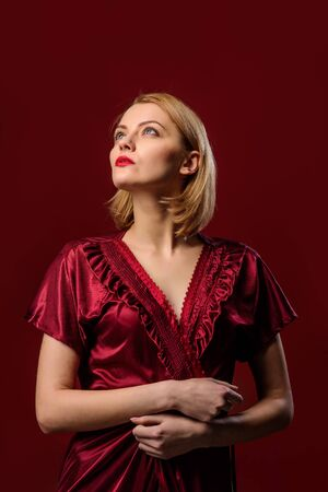 Young girl in sexy lace silk dressing gown. Sexy attractive blond girl wearing night gown. Woman in sexy burgundy sleepwear. Beautiful satin sleepwear for lady. Banco de Imagens
