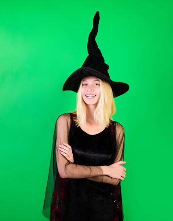 Pretty happy woman dressed as fairy with crossed arms. Smiling fairy enchantress in witch hat. Carnival costumes. Sexy enchantress in black dress with folded arms. Magical witch girl in black hat.