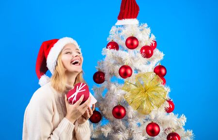Christmas shopping. Beautiful x-mas woman holding gift box. Sexy blonde young woman with Christmas present box. Christmas winter happiness concept. Woman in Santa helper hat with presents gift box.