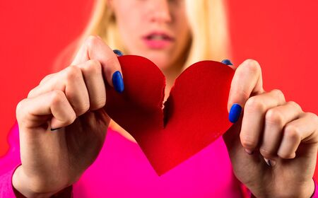 Broken heart. Close up photo of tearing red heart. Sad girl with red broken heart. Relationship problems. Break of relationships. Unrequited love. Selective focus.