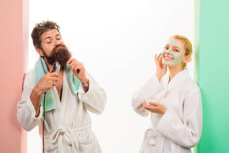 Morgenroutine. Paare, die sich morgens im Badezimmer vorbereiten. Mann, der Bart mit Trimmer rasiert, Frau, die kosmetische Maske auf Gesicht aufträgt. Schöner Mann rasiert Bart mit Elektrorasierer, Mädchen, das Gesichtsmaske anwendet. Standard-Bild
