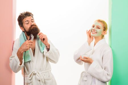 Morning routine. Couple preparing in bathroom in morning. Man shaving beard with trimmer, woman applying cosmetic mask on face. Handsome man shave beard with electric razor, girl applying facial mask.
