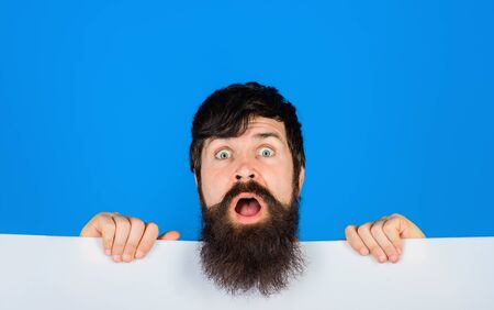 Surprised bearded man holding advertising board. Advertising and sale. Online shopping. Advertising banner. Seasons sale. Discount. Black friday. Marketing. Add. Copy space for text.