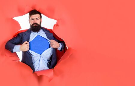 Through paper. Business growth. Businessman. Bearded man looking through paper. Super businessmen showing blue shirt. Superhero. Superman Cape. Hero. Symbol S. Super power. 版權商用圖片