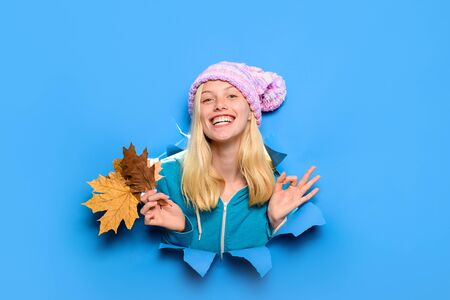 Beauty and fashion. Blonde girl showing ok sign. Autumn time. Season autumn holidays. Autumn clothes collection. Smiling girl shows ok sign. Girl with leaves looking through paper hole. Smiling girl