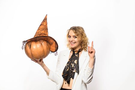 Happy Halloween. Emotional woman in witch Halloween costume with jack o lantern. Happy girl witch with pumpkin. Smiling girl in witch hat with pumpkin. Preparation Halloween holidays. Halloween party