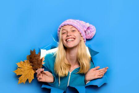 Moda donna. Sconto. Saldi stagionali. Saldi autunnali. Donna sorridente in cappello con foglie di acero. Donna felice con la foglia che guarda attraverso il foro della carta. Umore autunnale. Foglia d'acero gialla. Ragazza con foglie d'autunno Archivio Fotografico