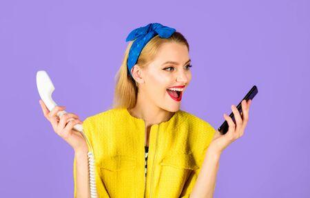 Une femme souriante en bandeau tient le combiné et le smartphone. Téléphones de différentes générations. Pin-up avec retro phone&mobile phone. Évolution technologique. Une femme élégante détient un téléphone filaire et un téléphone portable.