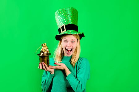 Saint Patrick's Day. Happy girl in green hat holds pot with gold. Leprechaun. Irish Traditions. Green top hat. Green hat with clover. Leprechaun costume. Clover. Patricks Day. Pot with gold.