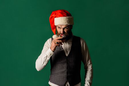 Businessman in Santa hat holds glass of wine. Man in waistcoat drink glass of red wine. Santa man tasting red wine. Handsome rich man with stylish mustache and beard hold glass&sniff smell of red wine