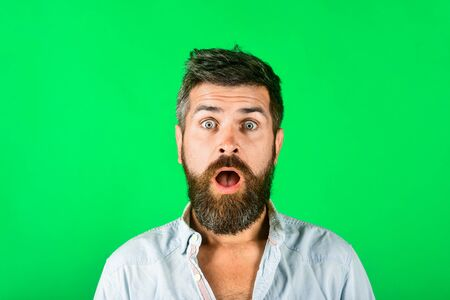 Surprised bearded man with long beard mustache. Astonished man in casual clothes. Amazed fashionable bearded male. Fashion model with stylish hair. Hipster in white shirt. Barber fashion and beauty.
