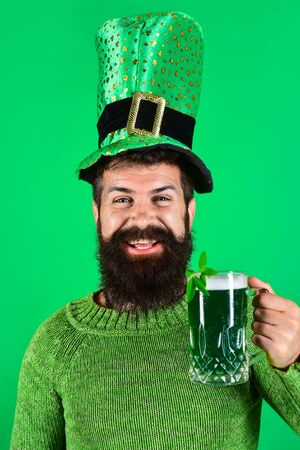Saint Patricks Day. Smiling bearded man in green top hat hold glass with beer. Saint Patricks Day symbols. Bearded man drinking beer in pub. Green beer. Patricks Day green shamrock. Irish traditions