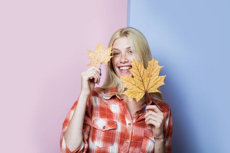 Fashion trends for fall. Smiling girl in casual wear playing with leaves. Blonde girl with golden leaf. Autumn woman. Autumn fashion. Autumnal mood. Autumn sale. Autumn woman with yellow maple leaves Stockfoto - 128606378