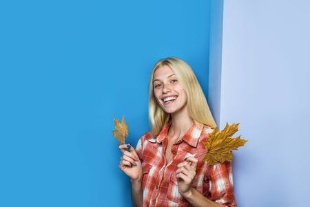 Smiling girl with golden leaf. Happy woman in casual wear holds leaves. Fashion trends for fall. Woman with golden maple leaves. Autumn fashion. Autumn girl. Autumnal mood. Autumn sales. Copy space 写真素材