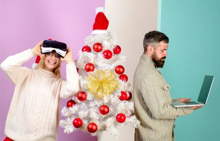 3d technology, virtual reality, family, winter, Christmas, New Year. Family in near Christmas tree. Happy family couple celebrate Christmas holiday. Woman in virtual reality glasses, man with laptop. Фото со стока
