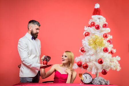 New Years Eve. Couple in love at Christmas or New year. Christmas tree. Family, presents, surprise, winter, happiness. Romantic relationships. Couple before New year at romantic dinner in restaurant.