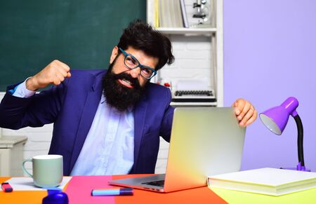 School student. Bearded male student in glasses. Student preparing for test or exam. Angry male university student near chalkboard in classroom. Teacher preparing for university exam. Exam in college