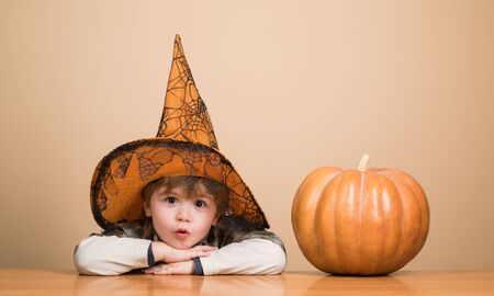 Happy Halloween. Cute boy in witch hat with halloween pumpkin jack o lantern. Boy dressed up trick or treating. Kid trick or treat. Halloween party. Preparation Halloween holidays. Child with pumpkin