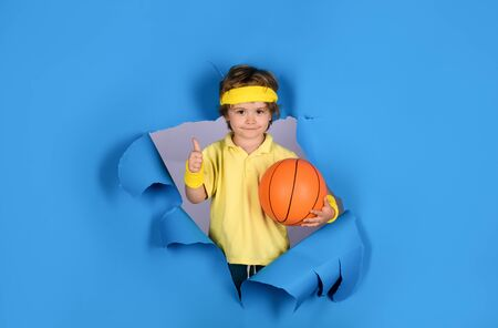 Basketball training game concept. Cute boy playing basketball. Enjoy sport game. Happy child holds ball shows thumb up. Kid activities. Little basketball. Sports equipment. Active sports lifestyle Stock Photo