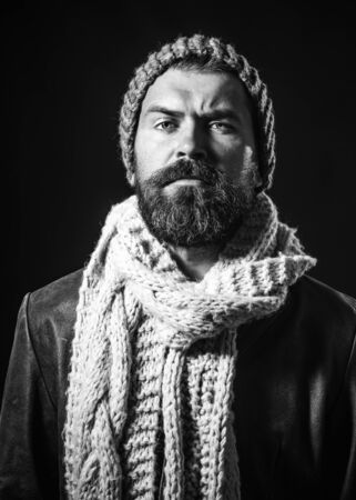 Warm clothes for cold season. Handsome bearded man wearing jacket, scarf and hat. Bearded man dressed in warm winter clothing. People, modern lifestyle, fashion and clothing concept. Perfect style 写真素材