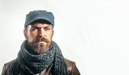 Handsome bearded man wearing autumn or winter clothing. Attractive man in warm knitted hat and scarf. Men autumn-winter fashion. Fashion handsome man in trendy sweater, scarf, jacket. Male fashion 写真素材