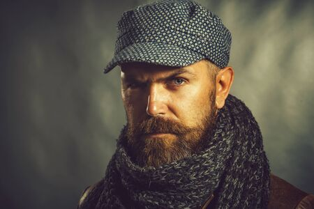 Fashionable demi-season clothing. Stylish man wrapped in scarf. Handsome bearded man wearing winter cap and scarf. People, lifestyle, seasons, fashion and clothing concept. Autumn or winter fashion