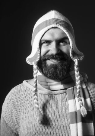 Autumn or winter fashion. Fashionable demi-season clothing. Stylish man wrapped in scarf. Handsome bearded man wearing winter hat and scarf. People, lifestyle, seasons, fashion and clothing concept