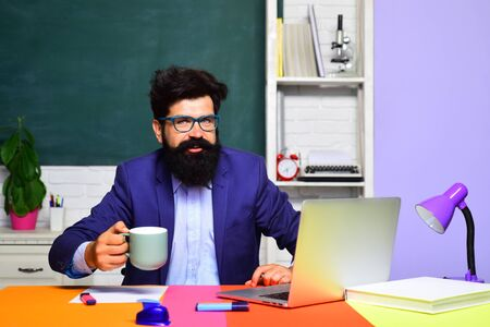 Young happy bearded teacher. Male student in university. Confident caucasian male teacher in auditorium. Education, knowledge concept. Educational process. Happy student drinks coffee. Back to school Stockfoto - 128606480