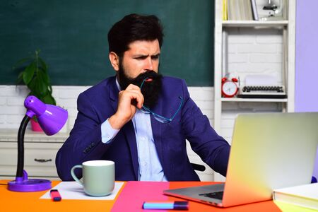 Young serious bearded teacher. Student preparing for test or exam. Back to school. Male student in university. Confident male teacher in auditorium. Education, knowledge concept. Educational process