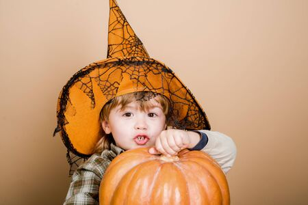 Happy Halloween. Cute boy in witch hat with halloween pumpkin. Jack o lantern. Trick or treat. Halloween party. Preparation for Halloween holidays. Child with pumpkin. Фото со стока