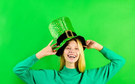 Green top hat. Blonde girl in in green top hat. Leprechaun. Green leprechaun. Green hat with clover. Saint Patricks Day. Traditions of Saint Patrick Day. Sale. Discount. Smiling woman Leprechaun costume.