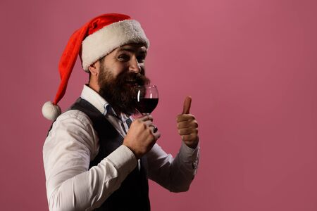 Bearded man tasting glass of wine. Degustation concept. New year party. ?heerful man holds wine&shows thumb up. Approval concept. Sommelier tasting red wine. Man in waistcoat drink glass of red wine. Фото со стока