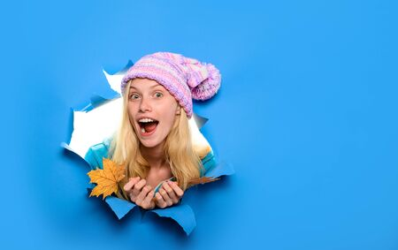 Surprised girl with leaf looking through paper hole. Autumn sales. Happy girl in hat with maple leaves.