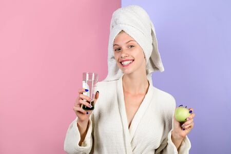 Morning routine. Awakening. Sleep. Smiling woman with apple and glass of water. Health. Healthy Lifestyle. Girl in a bathrobe. Morning treatments. Perfect morning. Stock Photo