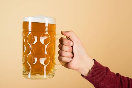 Fresh cold beer in glass in hand.   Man hand holds glass of draft lager beer. Oktoberfest. Beer pub. Bavarian service. Beer in mug with foam