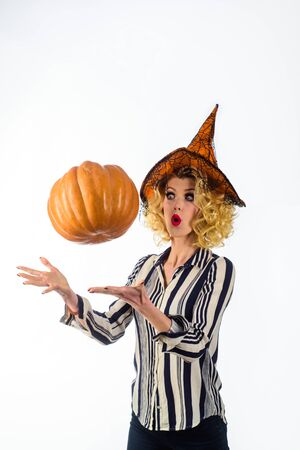 Halloween party. Surprised girl in witch hat with pumpkin. Preparation Halloween holiday.