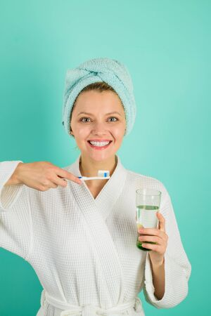 Happy woman with towel on head cleaning teeth with toothbrush. Girl getting ready to brush teeth with toothpaste. Beautiful woman cleaning teeth. Hygienic teeth cleaning every day. Dental hygiene.