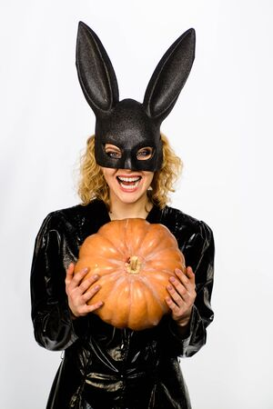Beautiful woman in halloween bunny costume holds pumpkin. Sexy blonde girl in rabbit black mask with pumpkin. Sexy female model in Easter bunny black rabbit mask with jack-o-lantern. Happy Halloween