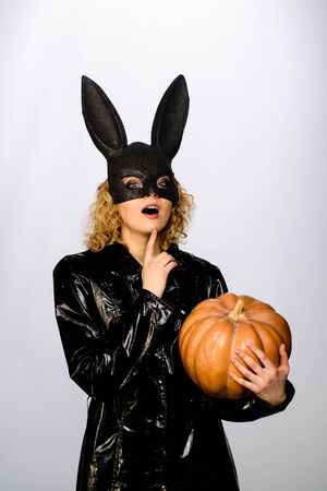 Happy Halloween. Beautiful woman in halloween bunny costume holds pumpkin. Sexy blonde girl in rabbit black mask with pumpkin. Sexy female model in Easter bunny black rabbit mask with jack-o-lantern