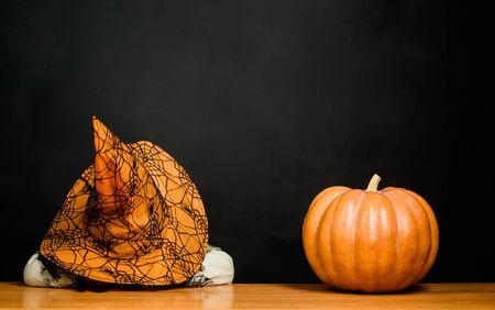 Jack o lantern. Niño cansado con sombrero de bruja con calabaza de halloween. Preparación para la fiesta de Halloween. Niño disfrazado de fiesta. Niño con calabaza. Truco o trato. Feliz Halloween. Disfraz de carnaval. Foto de archivo